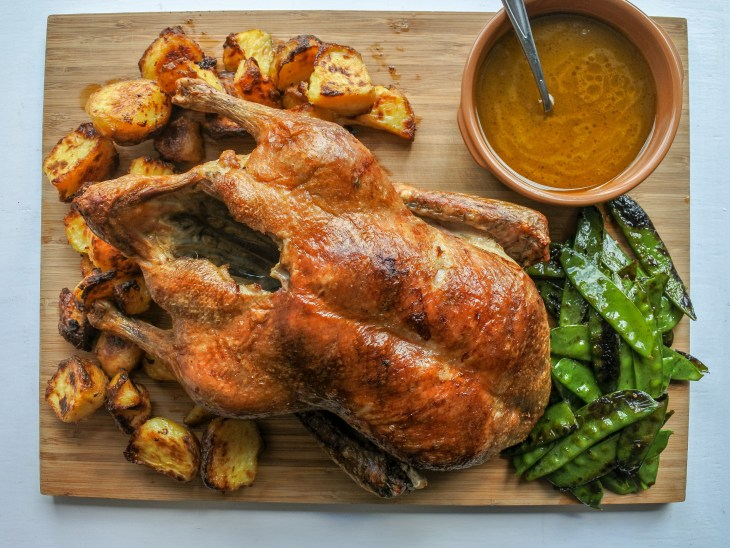 roast duck on a cutting board with roast potatoes, sauce and blistered snap peas