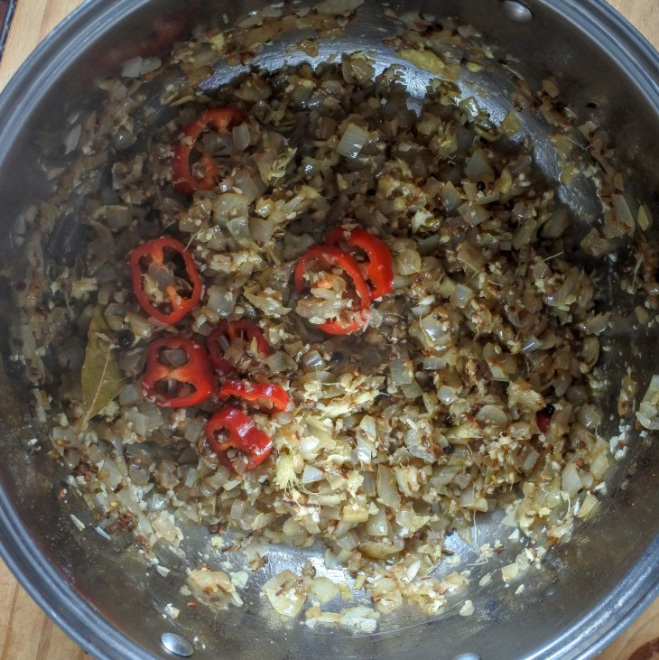 red chile, garlic, ginger and onions frying in a pan