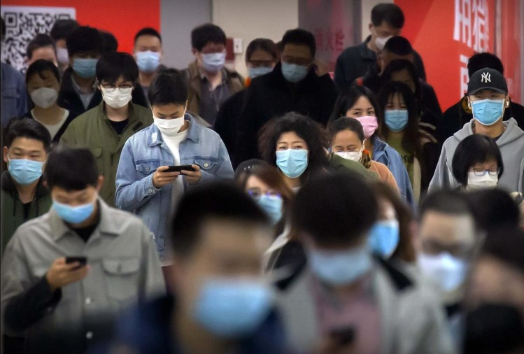 beijing commuters wear face masks to protect against the spread of new coronavirus as they walk through a subway station in beijing thursday april 9 2020 1586568658