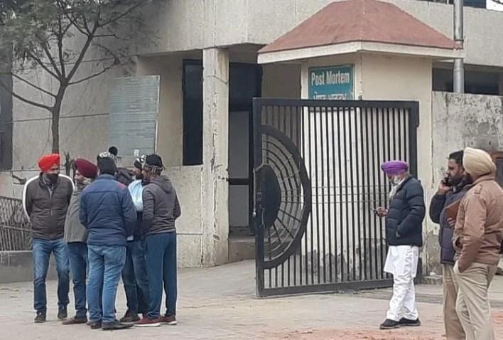 पोस्टमार्टम हाउस के बाहर खड़े लोग।