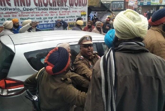 होशियारपुर में किसानों को शांत कराते पुलिस अधिकारी।