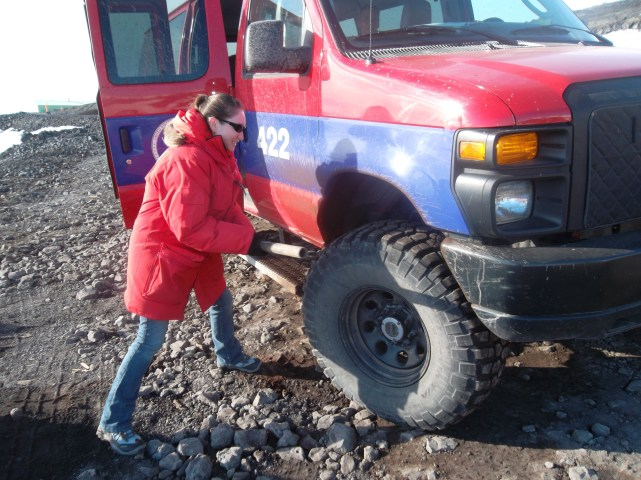 Johanna checks an item off her bucket list: knocking mud off the van in Antarctica.