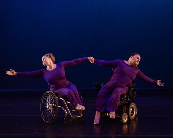 On stage, Frank Hull in his powerchair holds his arms extended and connected with dance partner in a manual wheelchair.