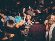 Busy party scene with laughing girl in centre of crowd.
