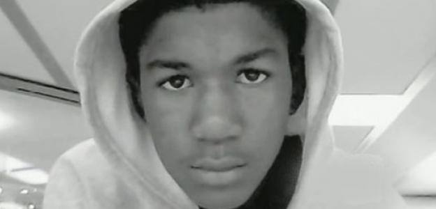 A close up of a young black boy's face, wearing a hoodie.