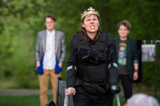 3 actors perform outdoors, under sunny green trees. Debbie is centre, snarling at the audience in a golden crown. She is using silver crutches.