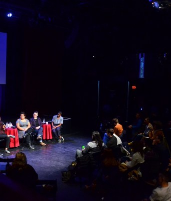 A panel of 6 speakers sits in front of a lit stage. An audience watches them attentively in the darkness.