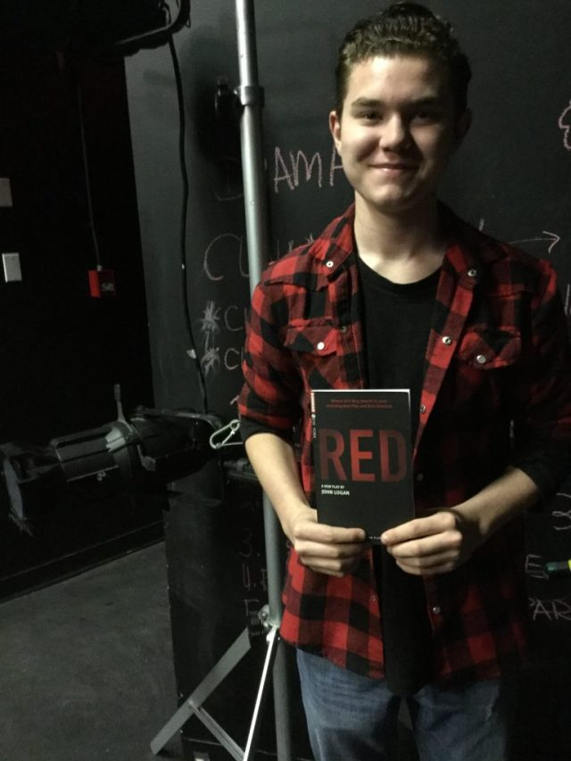 Trent, high school boy, holding a copy of the script for Red by John Logan.