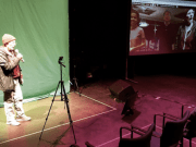 Sarah Garton Stanley stands in front of a green screen, video monitor shows people gathered in the digital rehearsal hall.