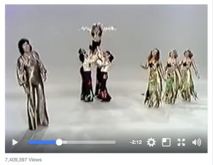 Screen capture of a vintage Spanish music video. One man in gold lameé jumpsuit sings, four men link arms to throw a third into the air with his arms outstretched like a bird, three women in sparkly gowns dance in unison.