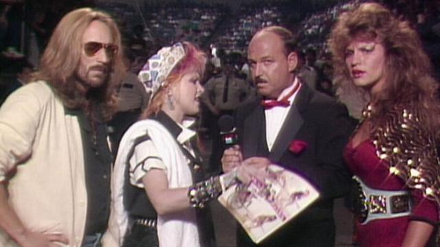 Four figures gathered around a microphone. Cyndi Lauper speaks into the microphone as the other three individuals look at the camera, somewhat surprised.