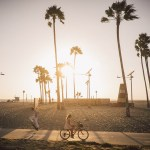 Biker and skateboarder in Venice Beach, Los Angeles, California at sunset