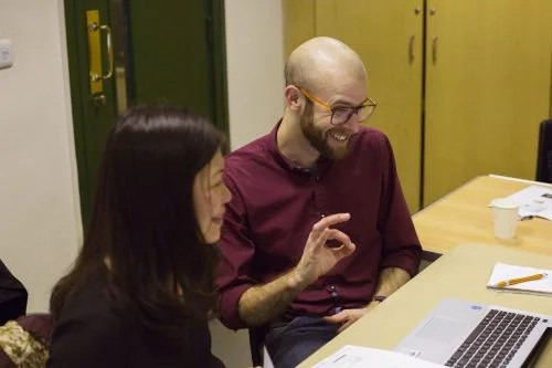 """A woman and a man sit at a desk, evidently collaborating on work on a laptop. The woman is smiling and the man is grinning and making an """"A-OK"""" hand gesture."""