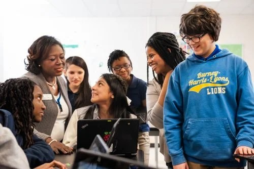 A group of young people and educators smiling while engaging with a computer