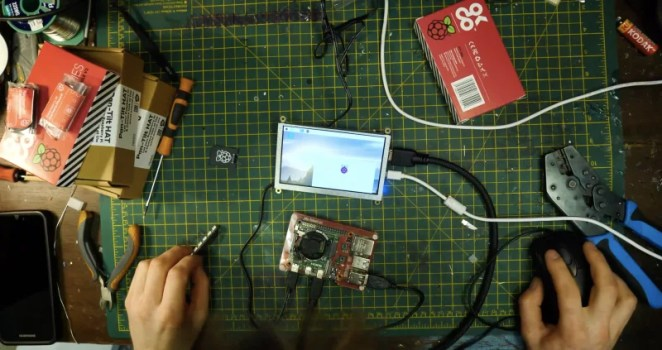 Raspberry Pi with camera module attached to small screen loading software needed to run face recognition