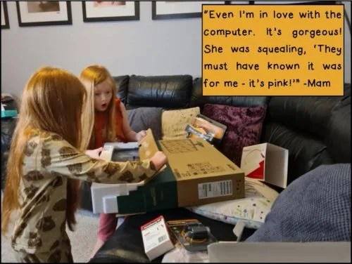 Two young girls unpack a computer display