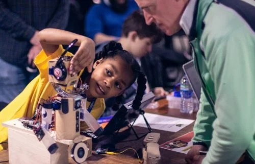 A girl shows off a robot she has built