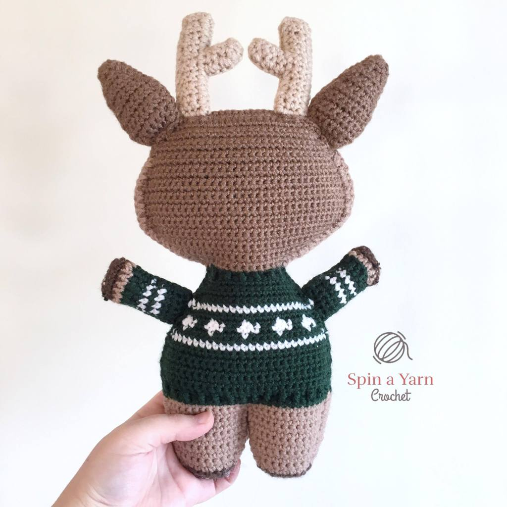 Back view of reindeer wearing green sweater