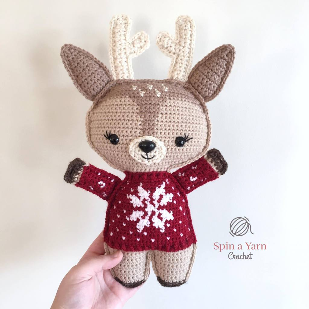 Reindeer with red sweater held in air