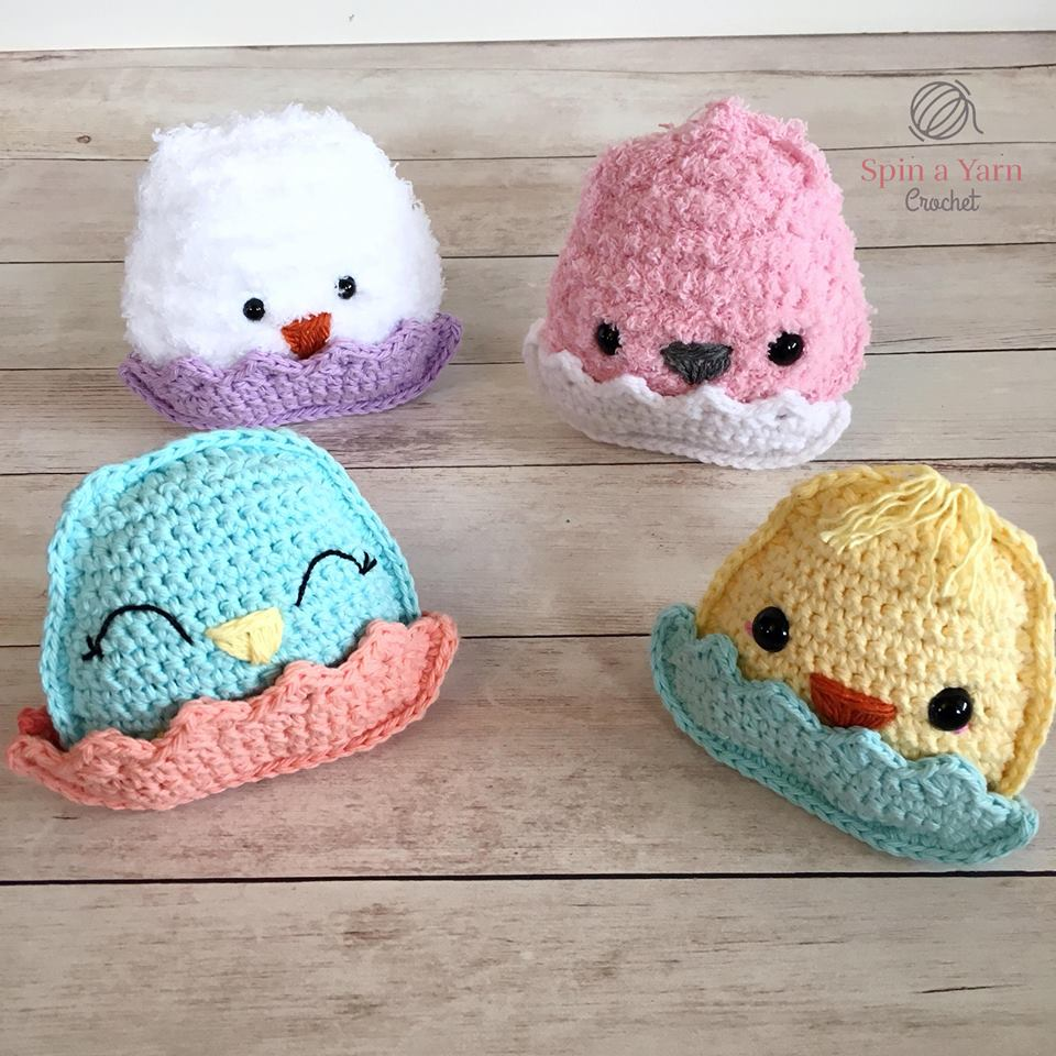 Four chubby crochet chicks sitting in eggshells