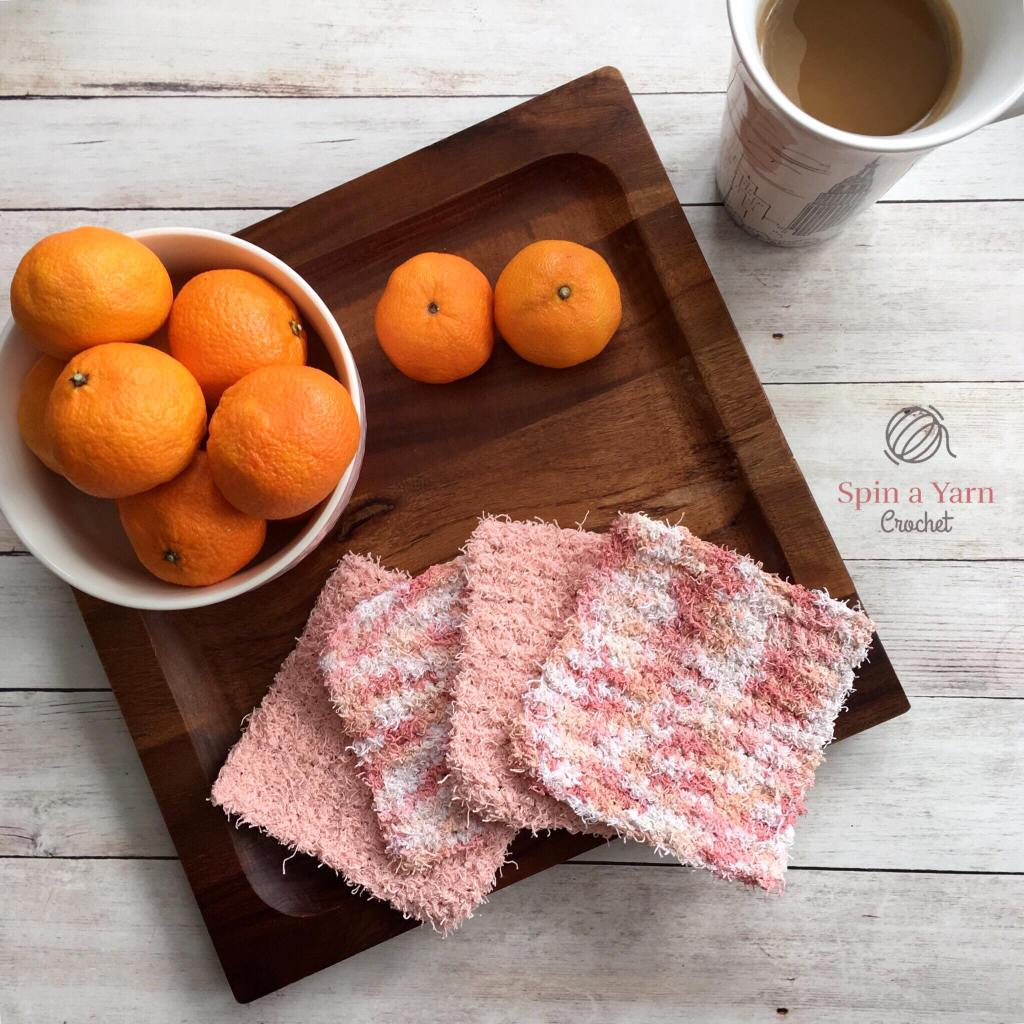 Four dish scrubbies with bowl of oranges