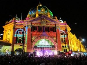 Flinders Street Station lit-up with a band playing on a stage at the entrance