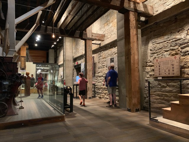 Photo of the inside of Mill City Museum. Exibits of old mill equipment is shown, surrounded by old brick walls and large wooden supports. Photo Credit:Spintheglobe.net