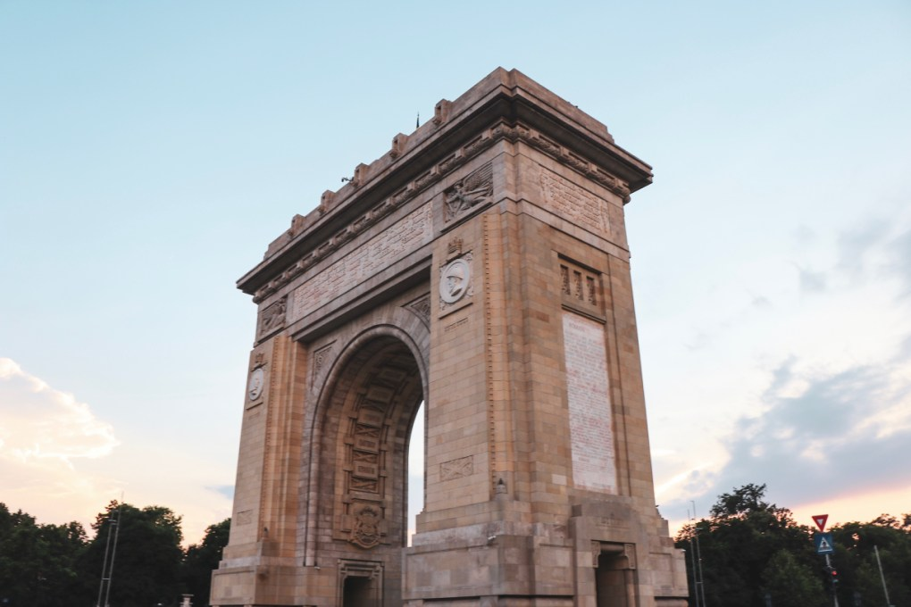 The arch of triumph is built from stone with ornate detail under the arch and along the top - the sky is blue behind it. 11 must-visit photo spots in Bucharest - spinthewindrose.com