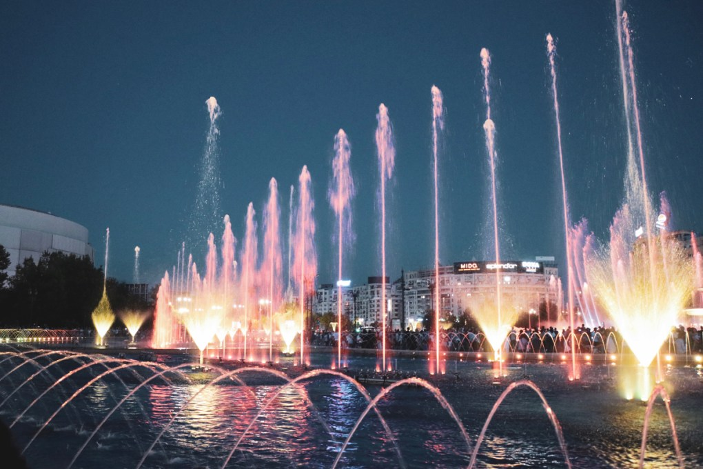 The fountains illuminate in different colours and a crowd watches in the distance. 11 must-visit photo spots in Bucharest - spinthewindrose.com