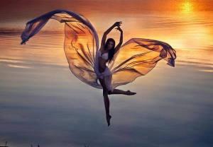 femme qui danse avec la mer, les ailes de son vêtement déloyé