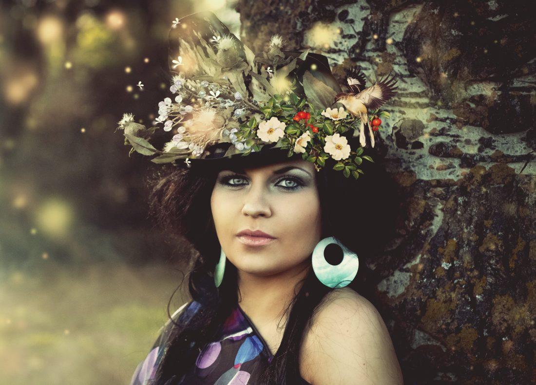Femme contre un arbre avec des fleurs dans les cheveux, très nature, Clairvoyance, chamane, extra-sensorialité, intuition
