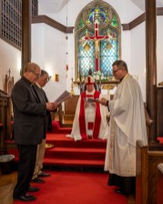 The Very rev. David Lynch and the Rev. Joe Behen present the Canons and Constitution. The Installation of the Rev. Isaac Petty as Priest in Charge at St. Luke's Episcopal Church, Excelsior Springs, Missouri. Image credit: Gary Allman