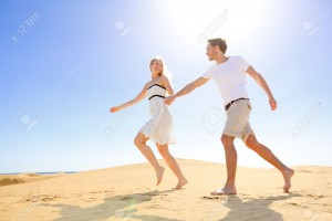 Relationship - happy couple playful romantic having fun under sun and blue sky in desert. Two young lovers running cheerful together on romance in summer. Cheerful Caucasian man and woman.