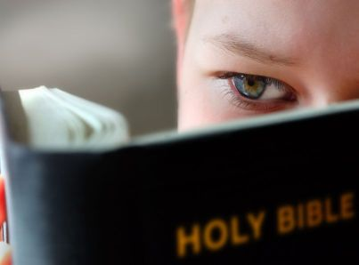 A child reading the Bible. A lectionary is a calendar of Bible readings.