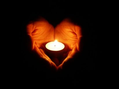 Heart-shaped hands holding a candle in the dark. Love God, love others.