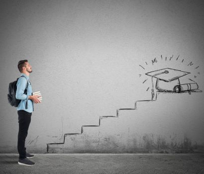 A man with books looking at a staircase leading to a graduation cap drawn on a wall.   Does faith formation mirror college as steps to success and graduation?