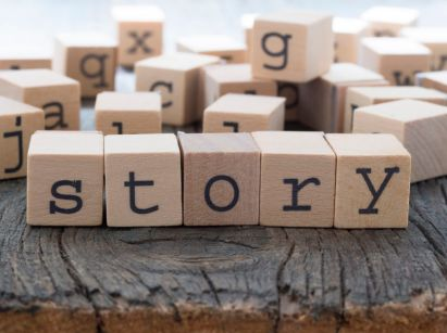 What are the power of stories in our lives? (An image of wooden blocks with letters spelling the word story.)