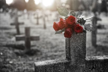 Red roses on a cross-shaped tombstone. Death will not have the final victory.