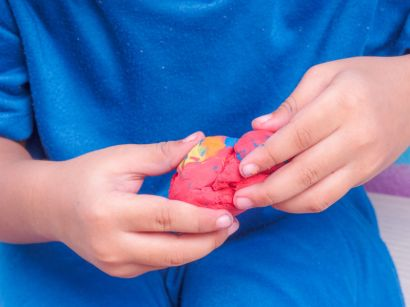 A child forming modeling clay just as we form faith at home.