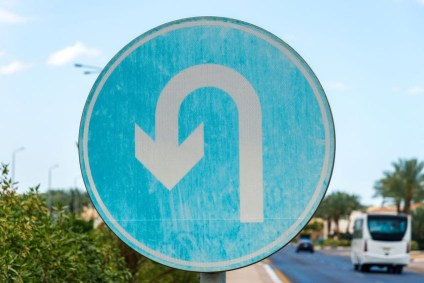 A blue U-turn sign on a roadway. Repentance is about a change of mind, a life u-turn.