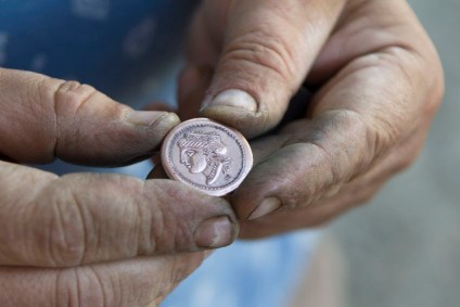 Hands holding a Greek drachma, like the woman's lost coin.