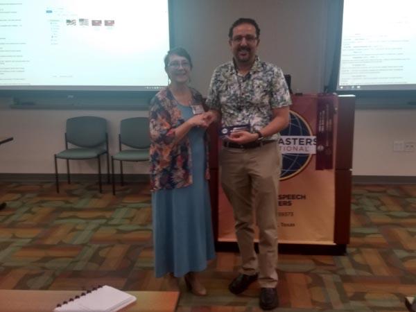 Sally awarding Usamah a ribbon for the completion of his CC education award