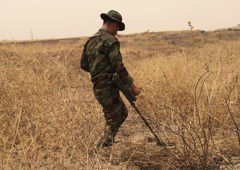 Peshmerga soldier sweeping for hidden explosives using a metal detector provided by SoA