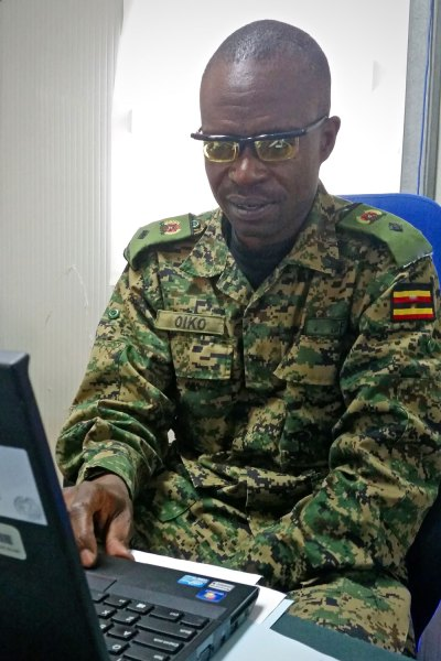 Colonel Oiko, wearing adjustable Adlens glasses, works on his laptop. Previously, his vision was so poor that he couldn't read his computer screen