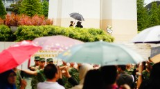 The wreath presented by the SAF is visible above all the umbrellas on a slightly wet February Friday