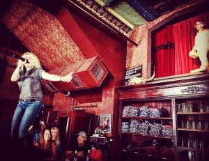 a female band member sings from the top of the bar