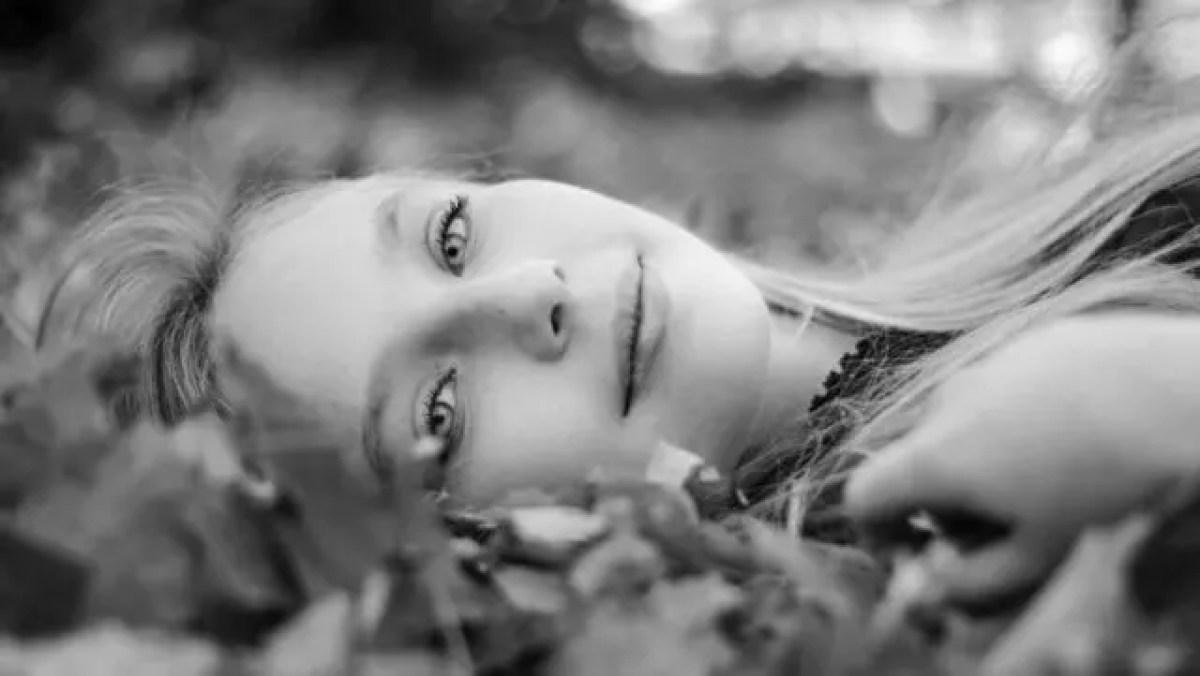 落ち葉に寝転ぶ女性
