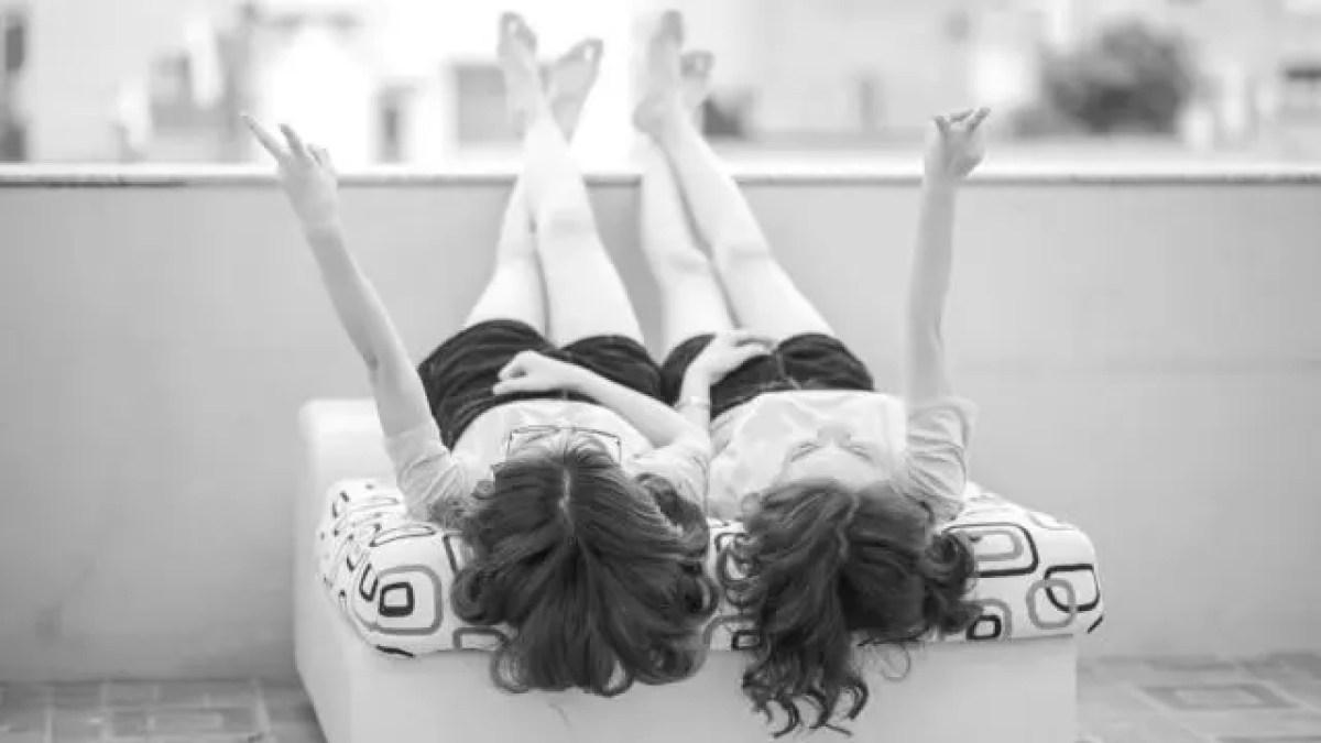 寝転ぶ双子の女性 ペアルック ピース