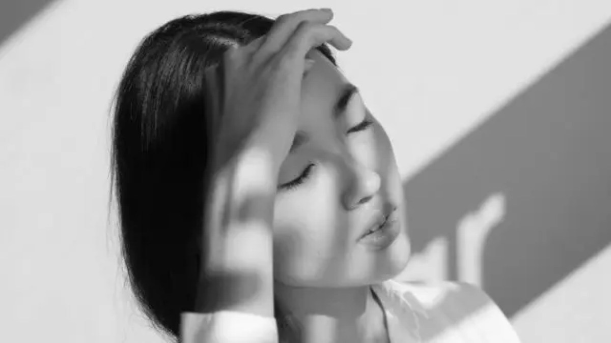 額を押さえる女性 頭痛 偏頭痛
