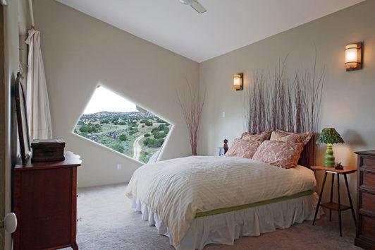 Το μοναδικό υπνοδωμάτιο του σπιτιού με το παράθυρο να ακολουθεί σε σχεδιασμό την κλήση της οροφής.